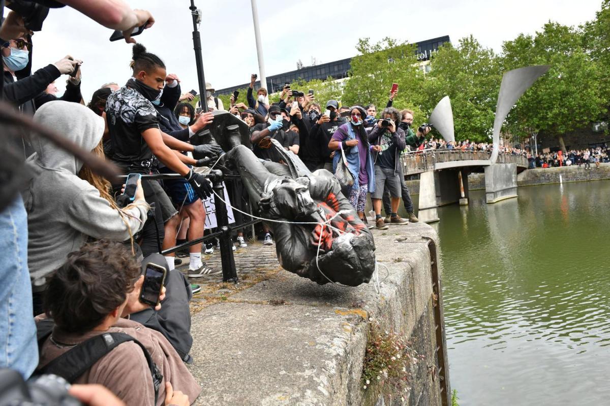 Manifestanti a Bristol con la statua abbattuta dello schiavista Edward Colston
